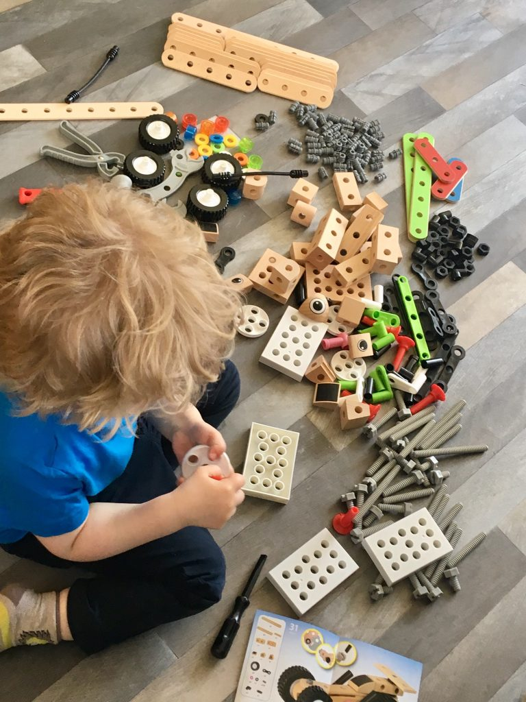 BRIO builder deluxe set Lucas is sat on a grey floor with blonde curly hair. Wearing dark pants and blue Tshirt. He is knelt over the various pieces of the set to make something. The camera is above him looking down