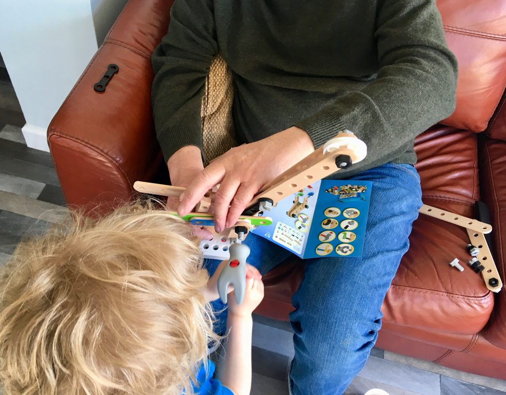 BRIO builder deluxe set review. Lucas is hammering a piece into the crane that my Dad is holding that they have just made