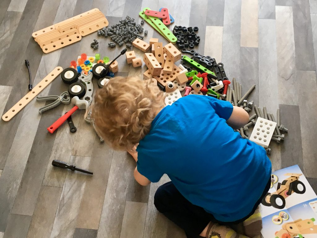 BRIO builder deluxe set Lucas is sat on a grey floor with blonde curly hair. Wearing dark pants and blue Tshirt. He is knelt over the various pieces of the set to make something