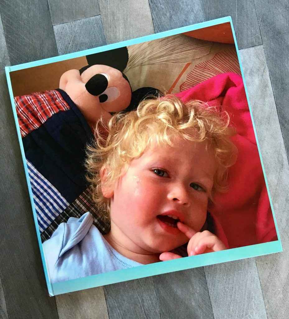 My-Picture.co.uk photo book. A photo of the front cover of the photo book showing Lucas looking up with blonde curly hair and a Mickey Mouse teddy next to him