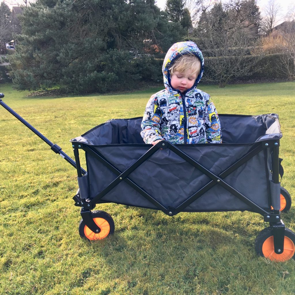 VonHaus camping folding cart review. You can see the full side of the cart, it is grey with black steel frame and orange wheels/ Lucas is sat in the cart and you can see a field and tree in the background