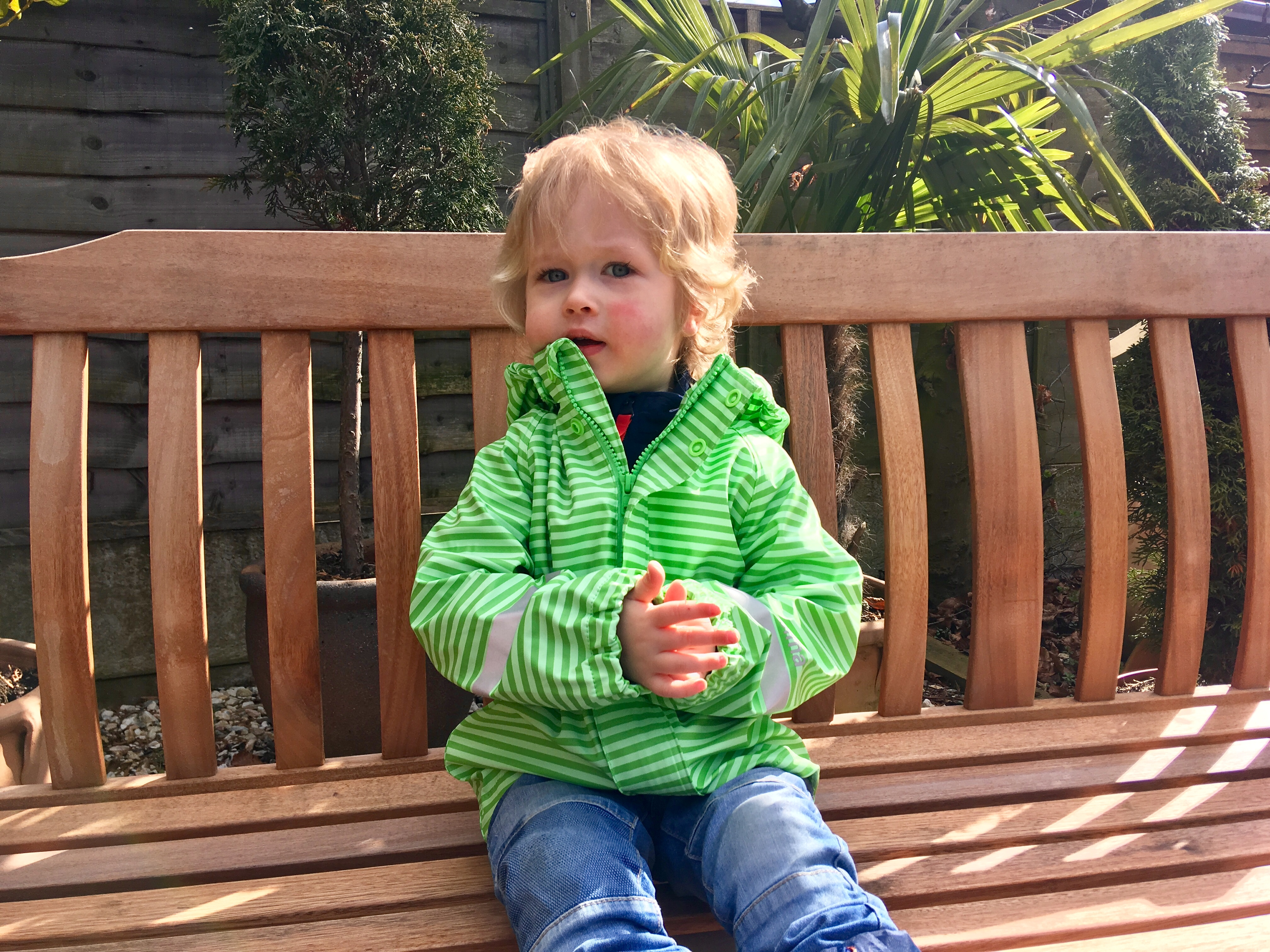 Reima jackets. Lucas is sat on a wooden bench in the garden. He is wearing a waterproof green stript jacket and blue jeans. He is looking slightly to the side and has blonde hair