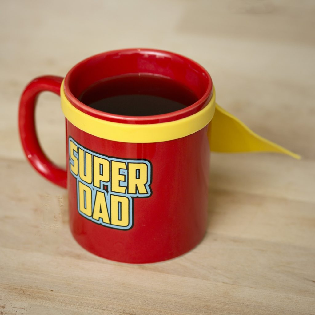 Father's Day gift ideas a red mug with super dad written in yellow and a yellow cape attached