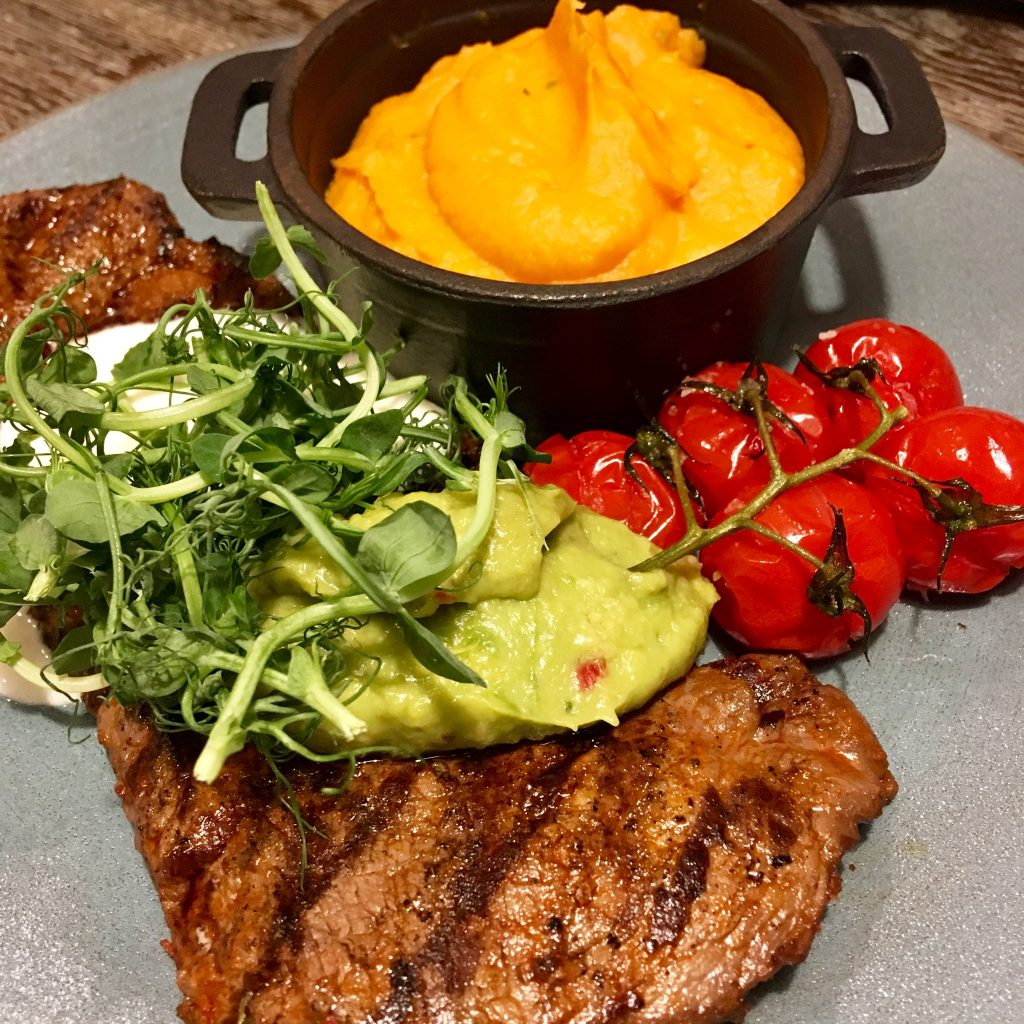 Blue Smoke on the Bay, Windermere review. A photo of a steak with guacamole and sour cream on top of it then with rocket leaves on top of that. The is a dish of sweet potato mash to the side and vine tomatoes