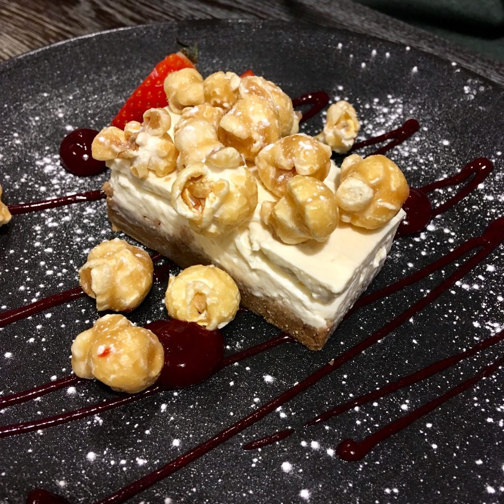 Blue Smoke on the Bay, Windermere review a rectangle piece of vanilla cheesecake with toffee popcorn on the top