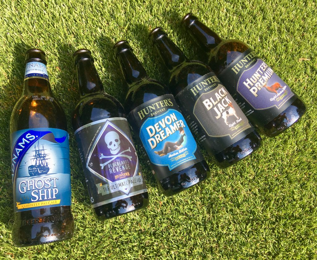 Hamper.com review a photo of 5 bottles of beer led on grass