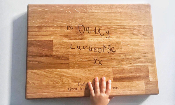 Father's Day gift ideas a photo of a wooden chopping board with handwriting carved in the middle and printed text at the bottom