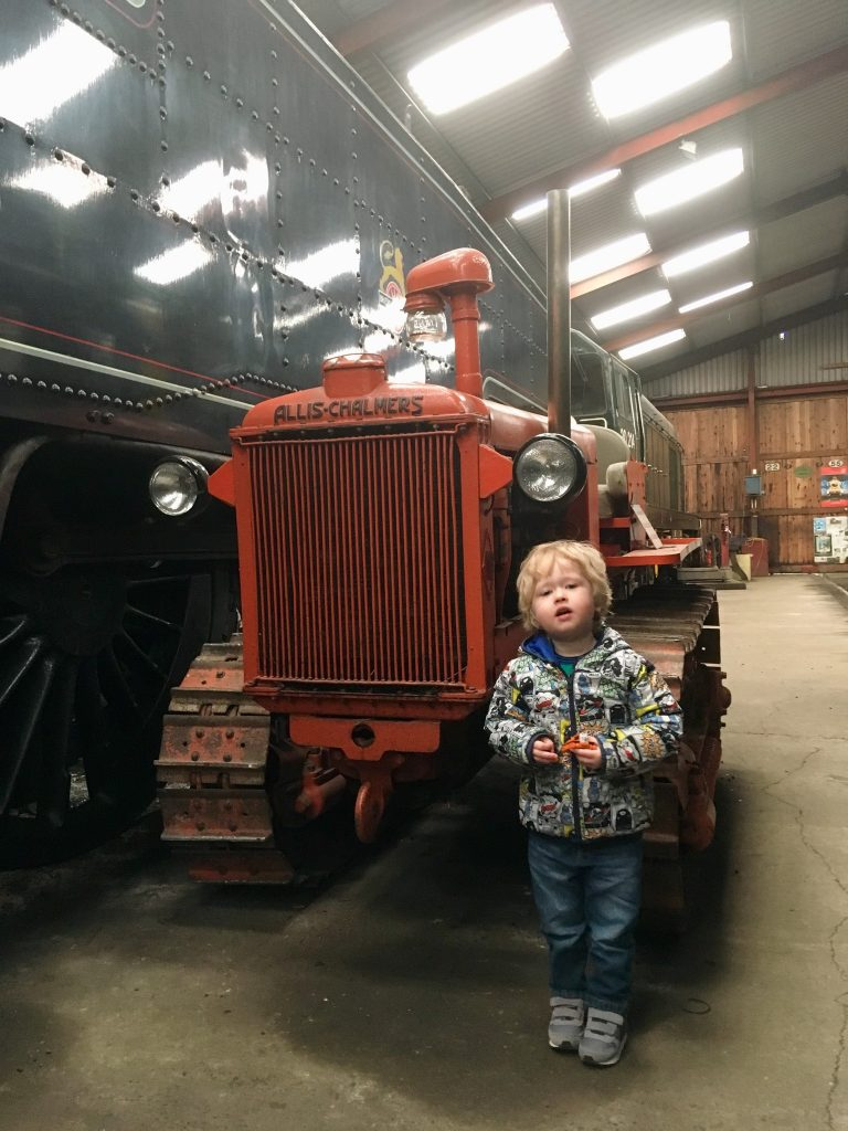 Lakeside and Haverthwaite Railway review Lucas standing next to an orange tractor in the sheds