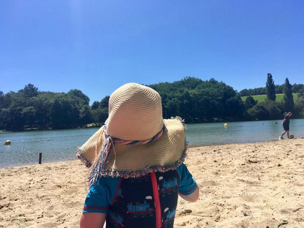 Summer essentials the back of Lucas who is wearing an all in one thomas tank engine sun suit and my straw hat looking out onto a lake day on sand