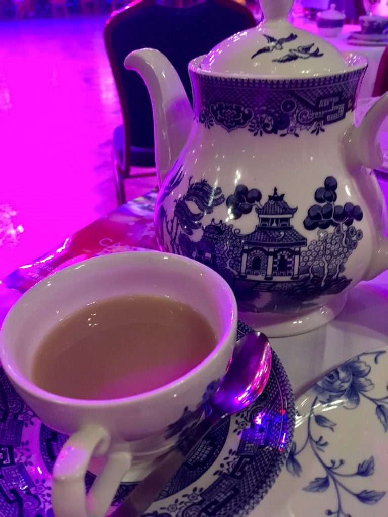 Afternoon Tea in Blackpool Tower Ballroom A tea pot and cup and saucer with tea in. The set is blue and white