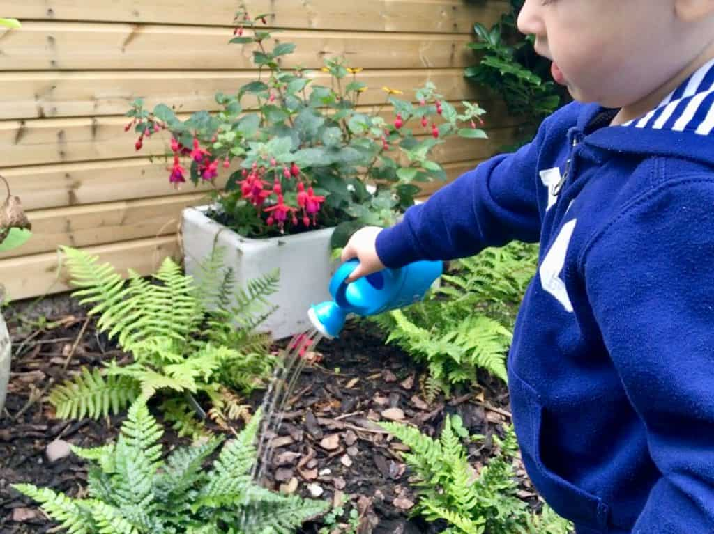 Celebrating outdoor play, every day Lucas watering plants with a small watering can