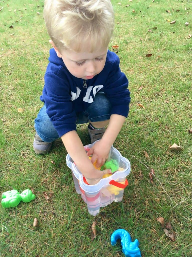 Celebrating outdoor play, every day Lucas is knelt down with his hands in a bucket of water playing with plastic toys