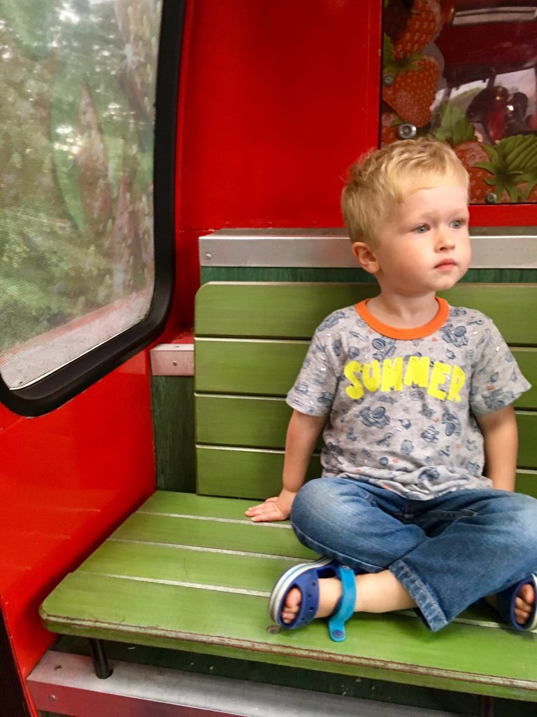 Lucas sitting on a tram on looking to the side