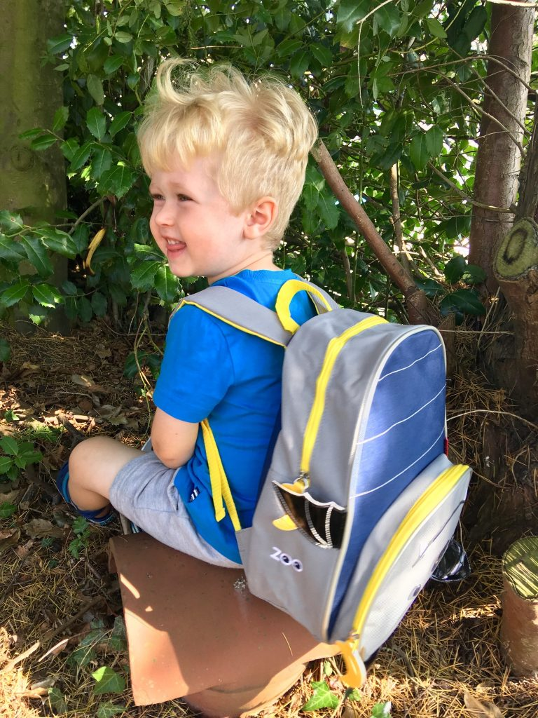 Skip Hop bags review Lucas is sat down wearing the bat backpack on his back and smiling