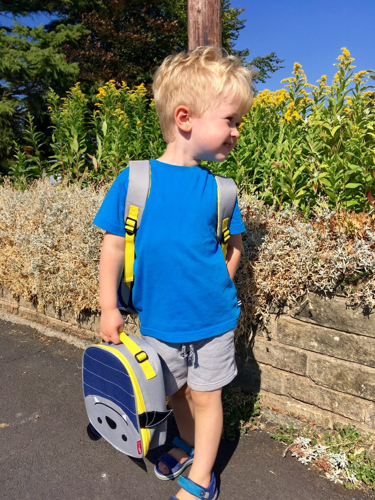 Skip Hop bags review Lucas is stood holding his bat lunch bag