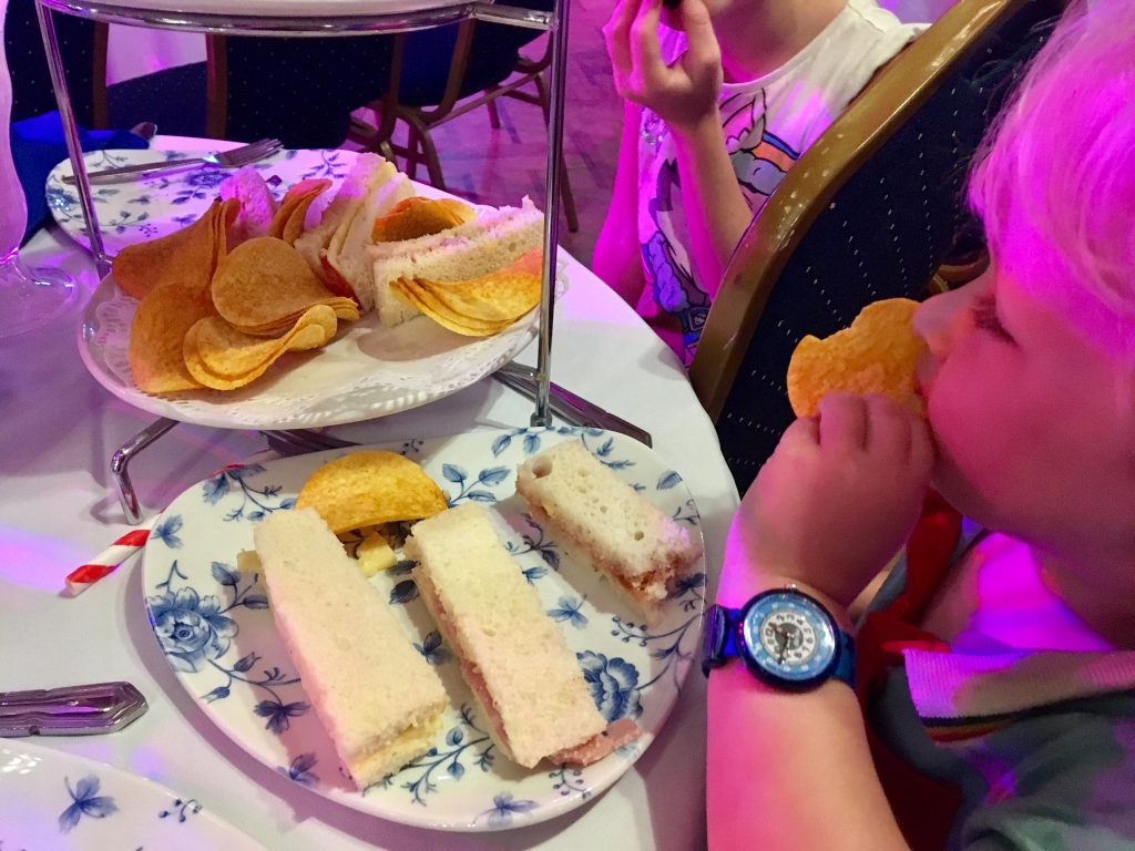 Afternoon Tea in Blackpool Tower Ballroom Lucas eating a sandwich with his plate and the afternoon tea stand in front of him