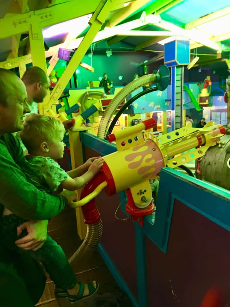 CBeebies Land, Alton Towers review. Lucas and D looking and aiming their ballroom shooter in Justin's house pie factory