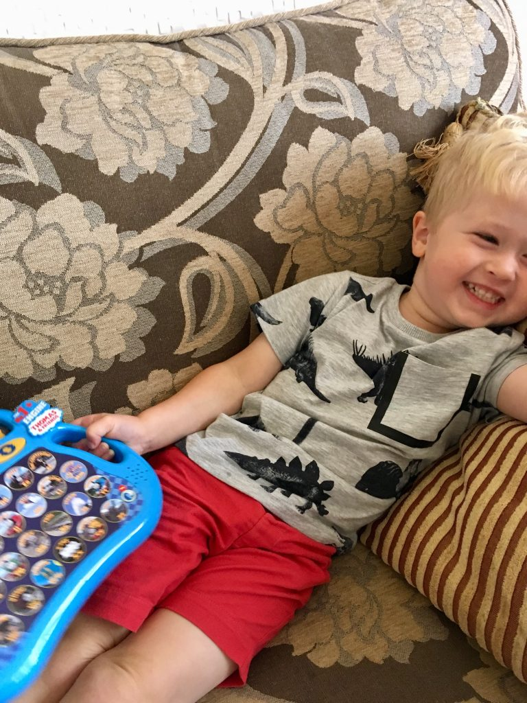 Thomas Alphaphonics review Lucas led on sofa laughing holding the Alphaphonics game