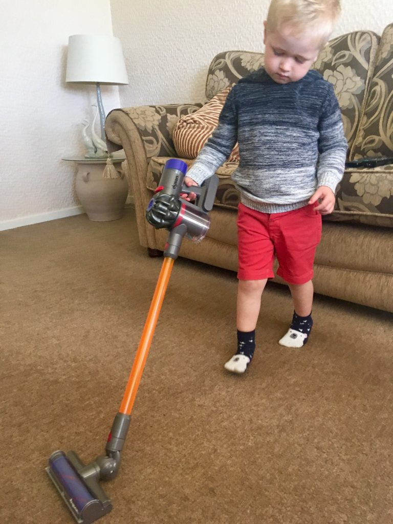 Casdon Dyson review Lucas using the vacuum with the long handle on the floor
