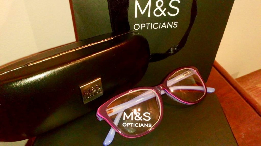 Marks and Spencer's Opticians purple glasses next to a branded Marks and Spencer's black glasses case and bag