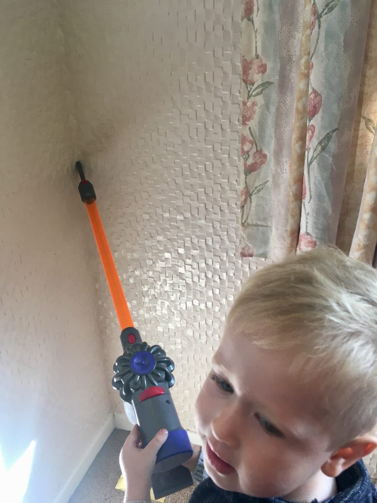 Casdon Dyson review Lucas is using the nozel attachment on hand hand Dyson against wall