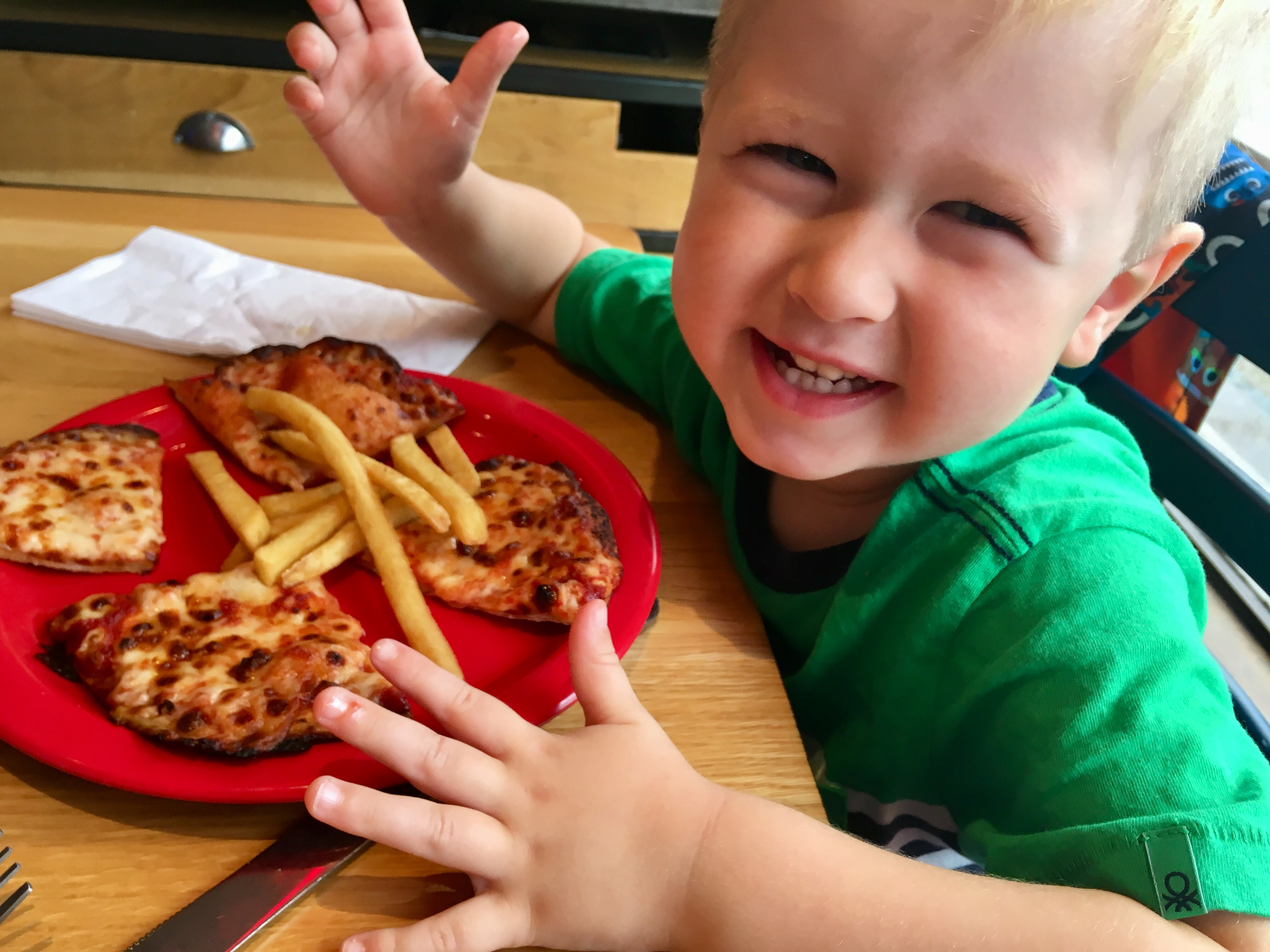 Epic Pizza's at Pizza Hut Lucas smiling at the camera with pizza and chips in front of him