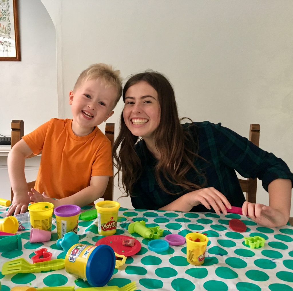 Lucas and his godmother sat at a table with play doh in front of them. They are both smiling at the camera