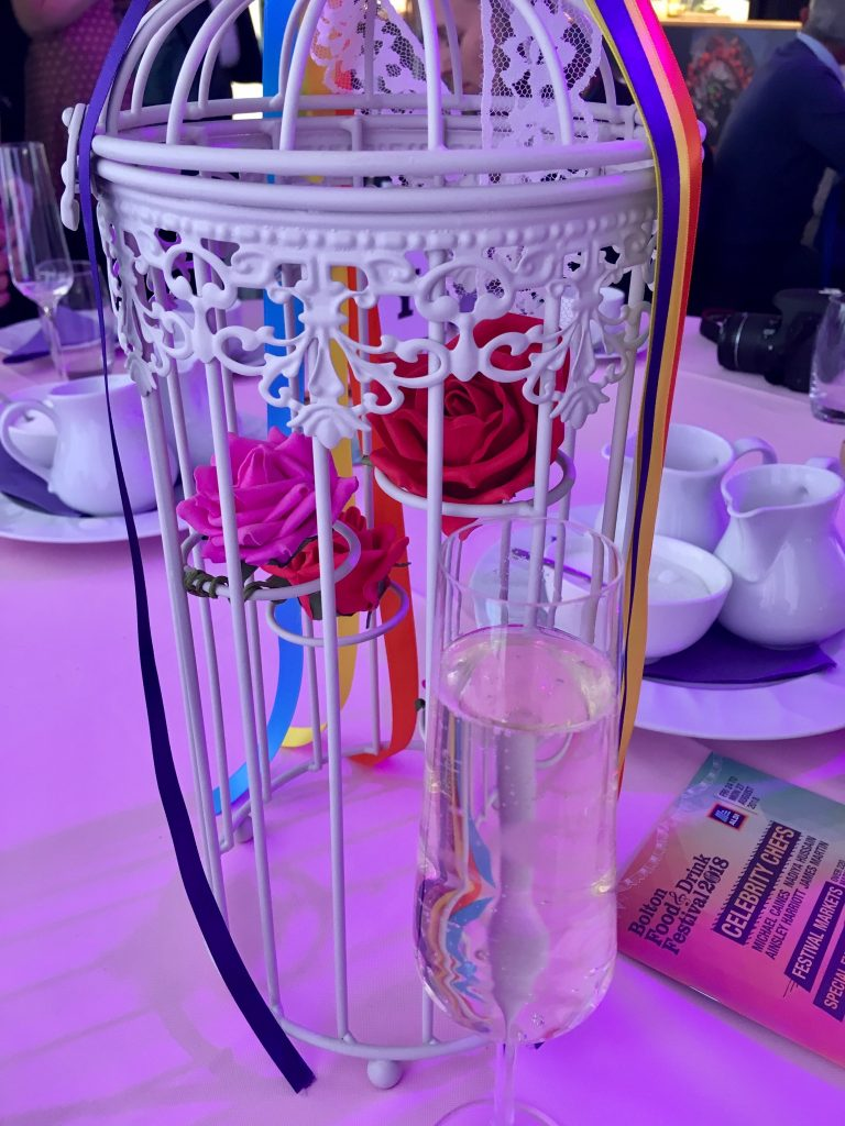 A glass of prosecco on a table next to a white bird cage with coloured roses in it