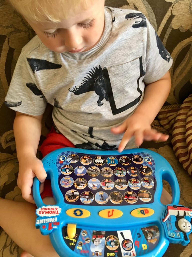 Thomas Alphaphonics review Lucas is sat on sofa with the game on his lap, he is looking at it and pressing a button