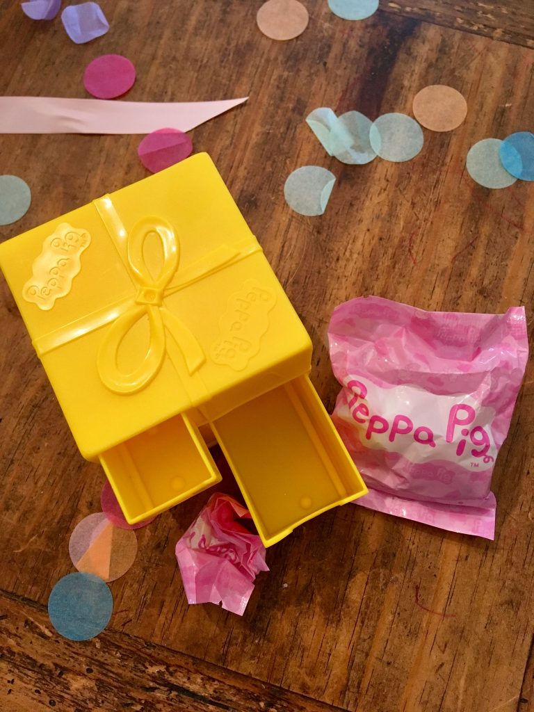 Peppa Secret Surprise review One of the surprise yellow plastic boxes with two drawers open and twos small pink packets next to ot