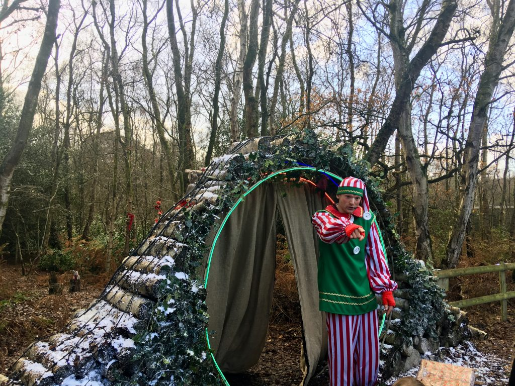 Blakemere Village, Christmas woodland review The elf in front of the circlular door going to the woodland