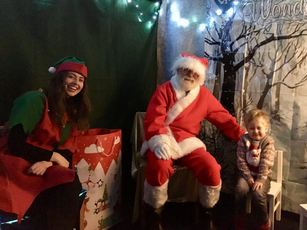 Organising a Christmas tree festival Lucas, Father Christmas and elf day in grotto smiling at camera