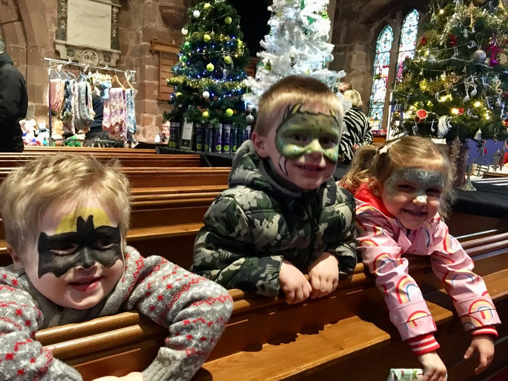 Organising a Christmas tree festival Lucas and 2 friends all smiling with different face paints on