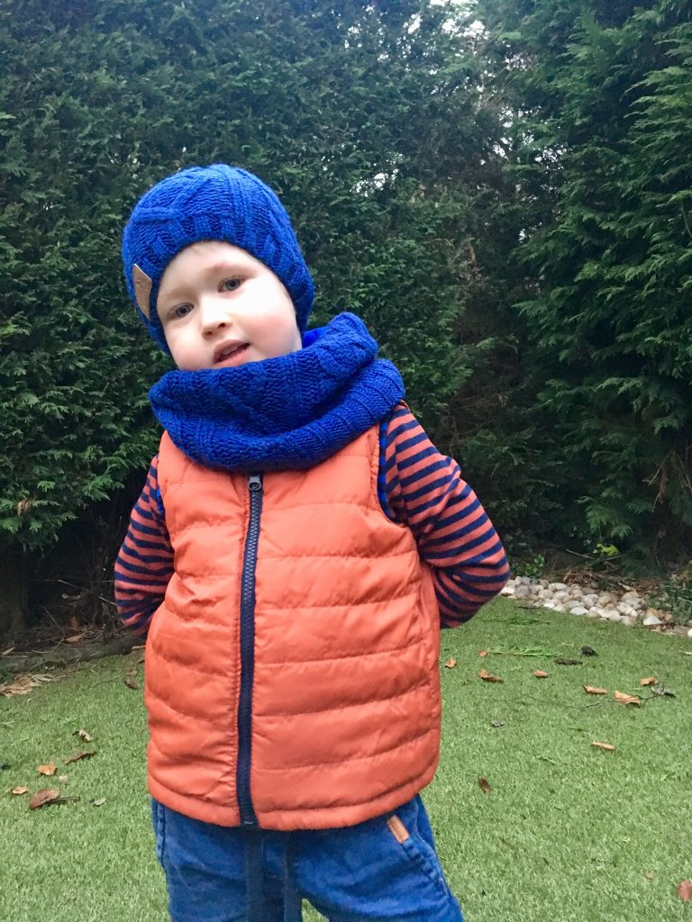 Vertbaudet Lucas is wearing a blue cable knit hat and snood over red gilet
