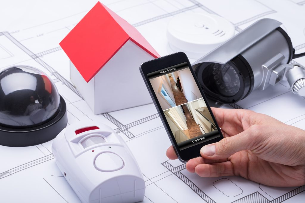 7 Things to Consider Before Buying a Home Security System. Photo of Architect Using Home Security System On Mobile Phone