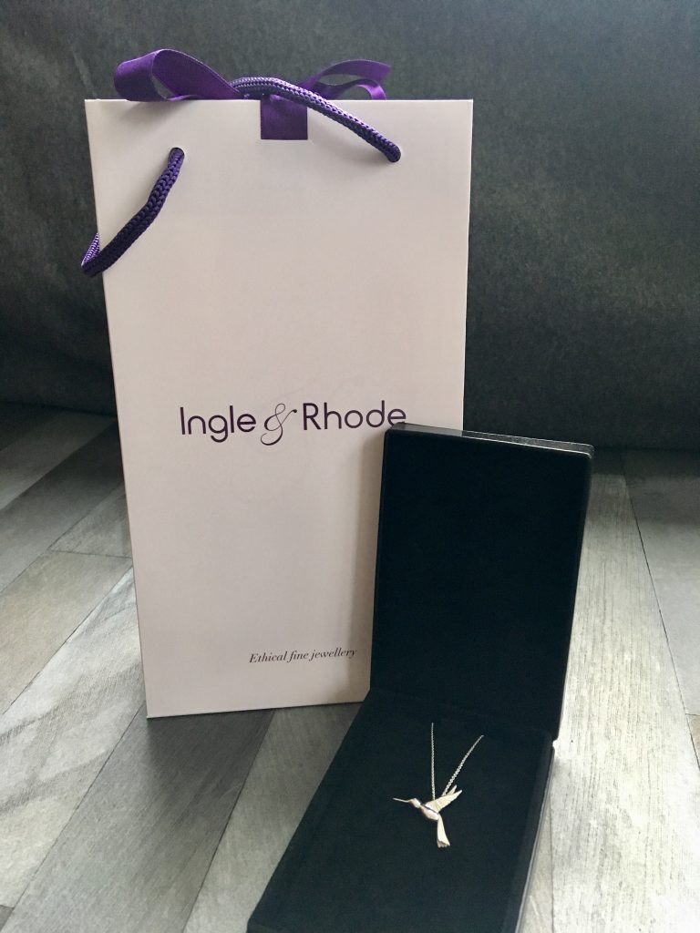 Ingle and Rhode review - the ethical jeweller. A white gift bag with purple ribbon and ingle and Rhode written in purple. The hummingbird is in a black case next to it