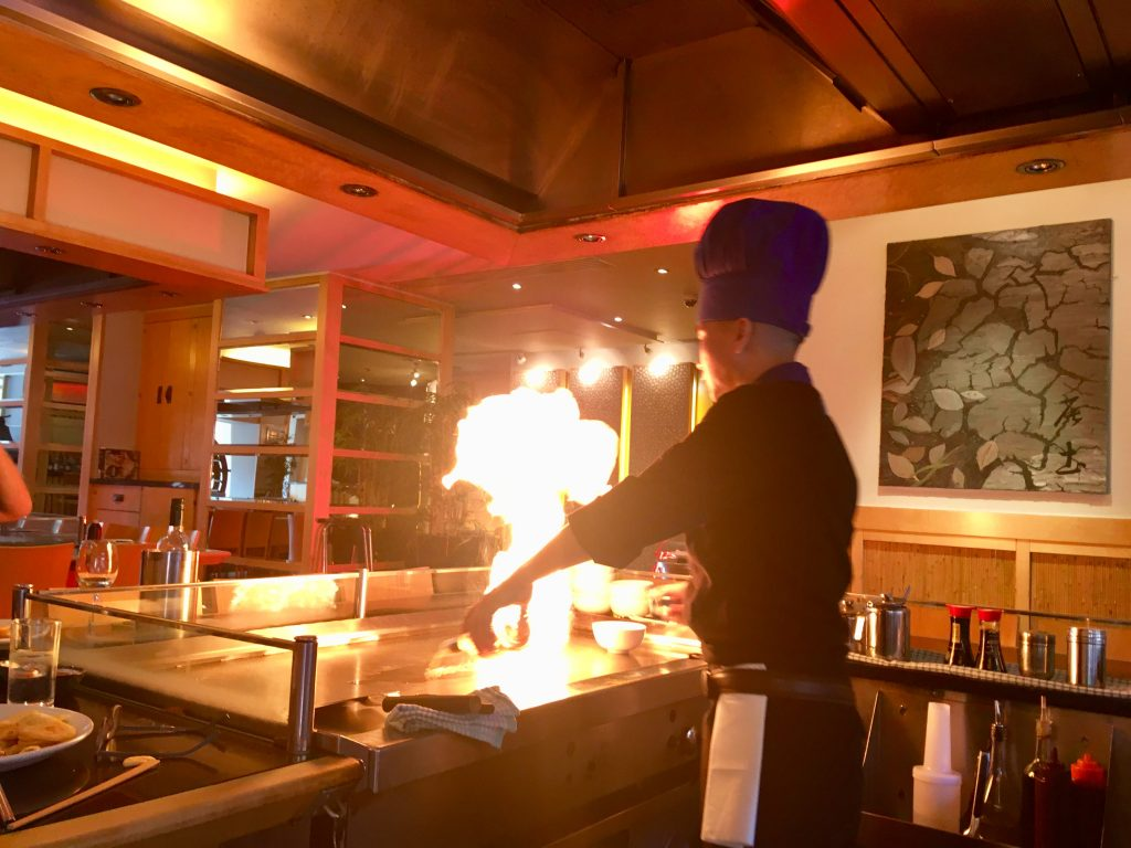 Sapporo Teppanyaki Manchester review. The chef is at the hot plate with huge orange flames
