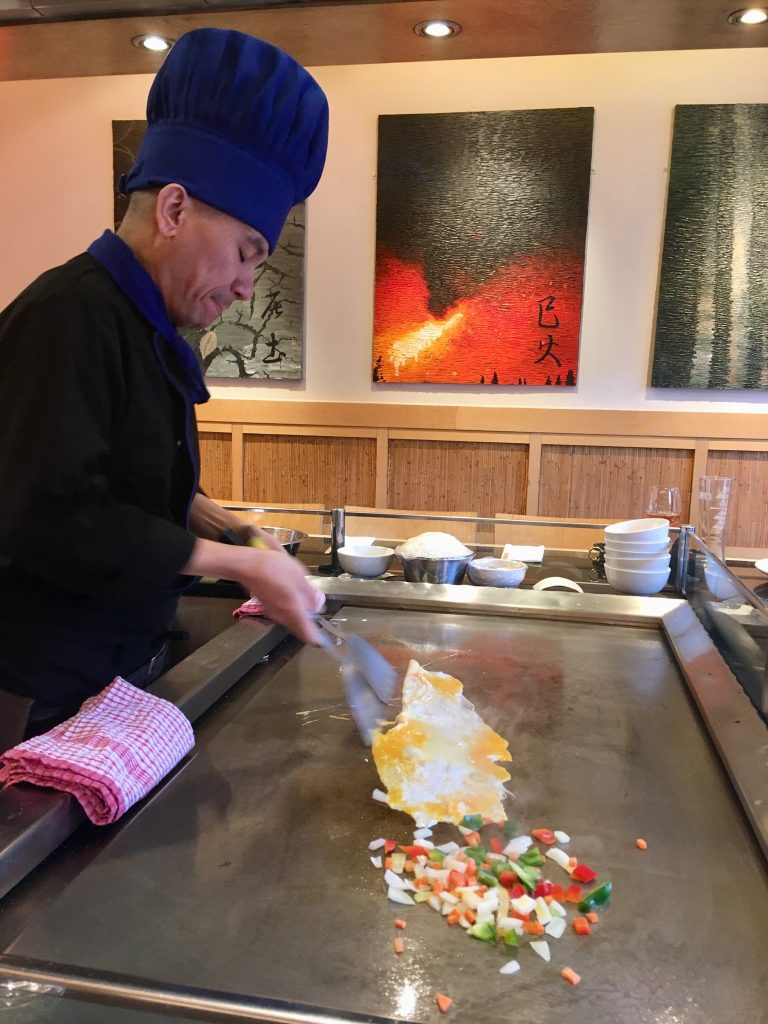 Sapporo Teppanyaki Manchester review. The chef is cooking egg fried rice on the hot plate