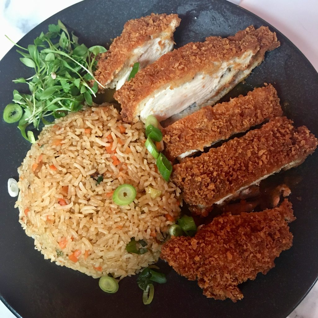 Liberté liverpool chicken katsu with a dome of rice next to it on a black playe