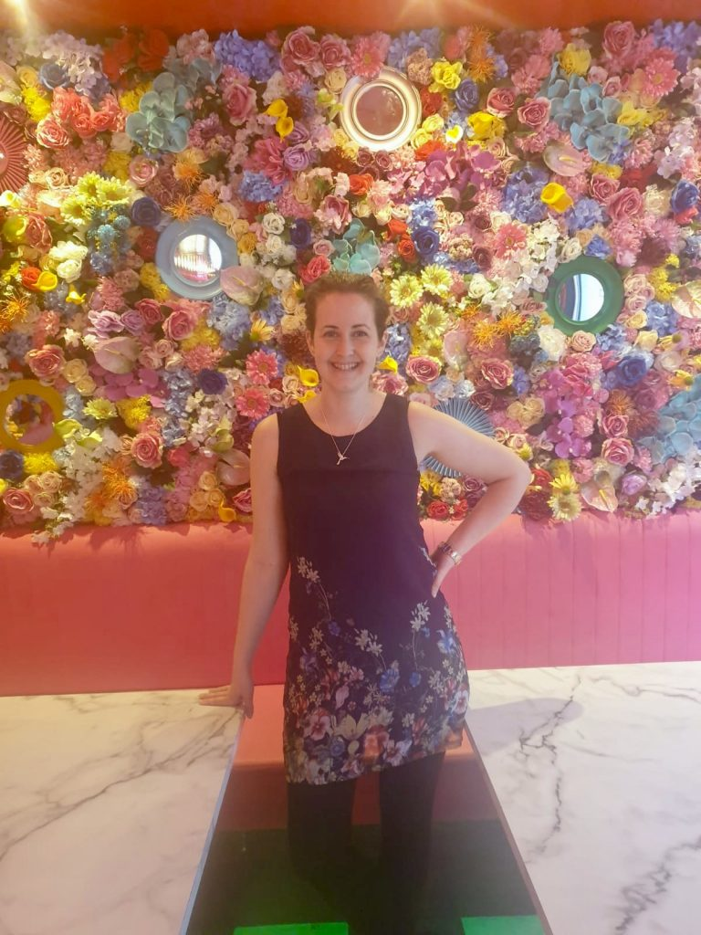 Liberté liverpool I'm stood smiling at the camera wearing a navy dress with flowers on the bottom of it. Behind me is a bright flower wall