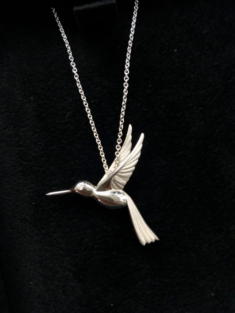Ingle and Rhode review - the ethical jeweller. Close up of silver hummingbird necklace with diamond eye against a black felt background