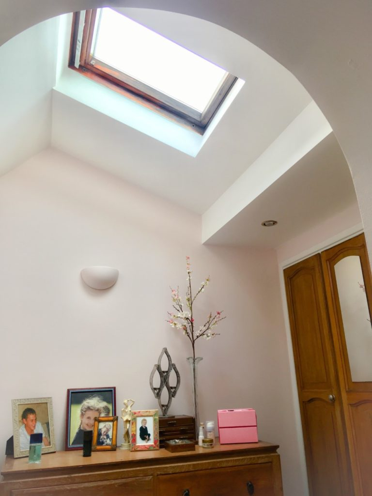 Brightening your home with VELUX roof windows. A single storey extension dressing room with a velux roof window. You can see wooden fitted wardrobes to the right and in front of you is a set of drawers with photos, jewellery box and accessories on