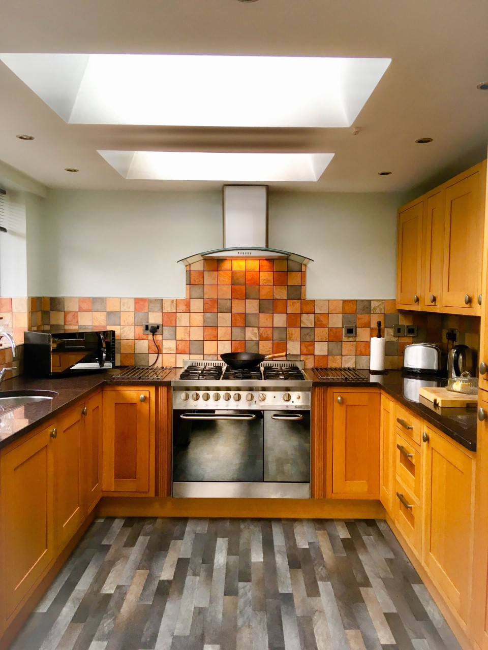 Brightening your home with VELUX roof windows. my kitchen with two velux roof windows, in front of you is a range cooker with tiles wall and at either side is wooden cupboards with granite worktop
