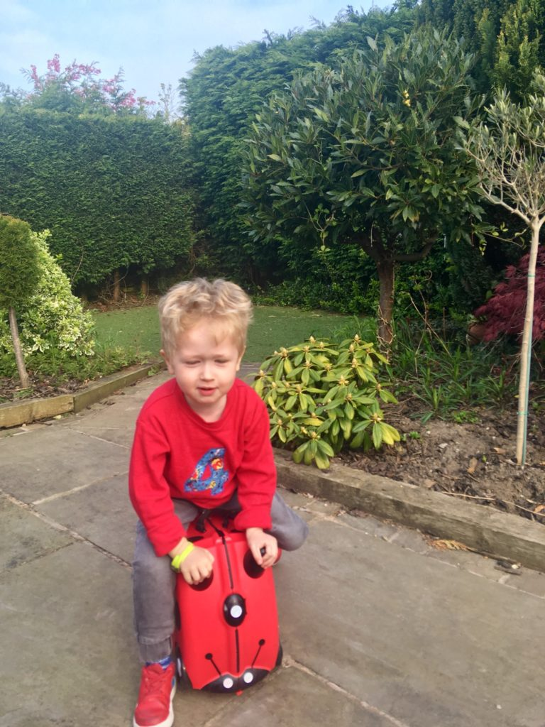 Travel with Trunki Lucas is sat on the Trunki rising it in the garden