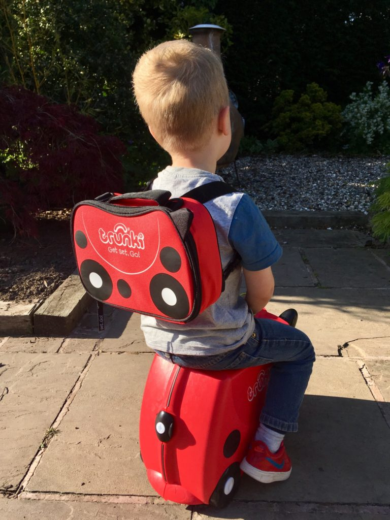 Travel with Trunki Lucas is sat on the Trunki, he is wearing the lunch backpack