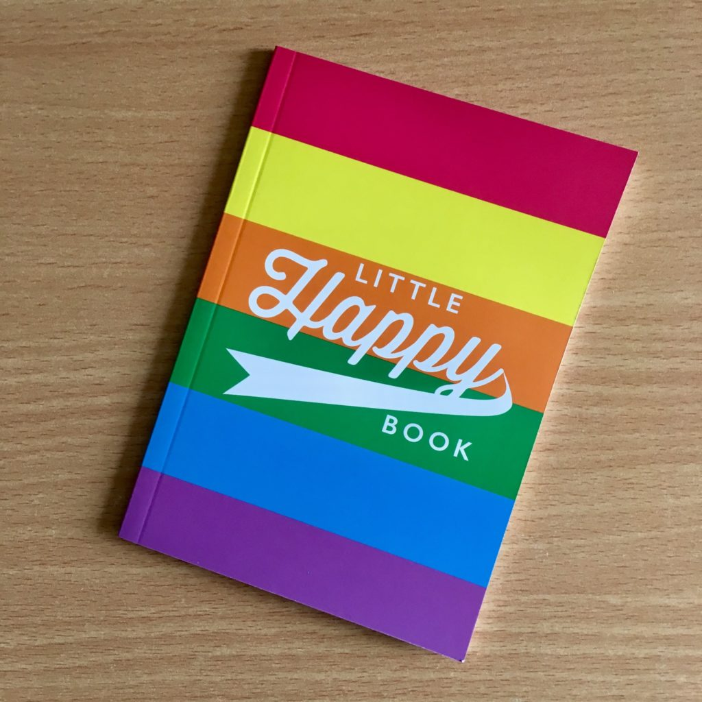 A stripy coloured notebook with white writing saying little happy book