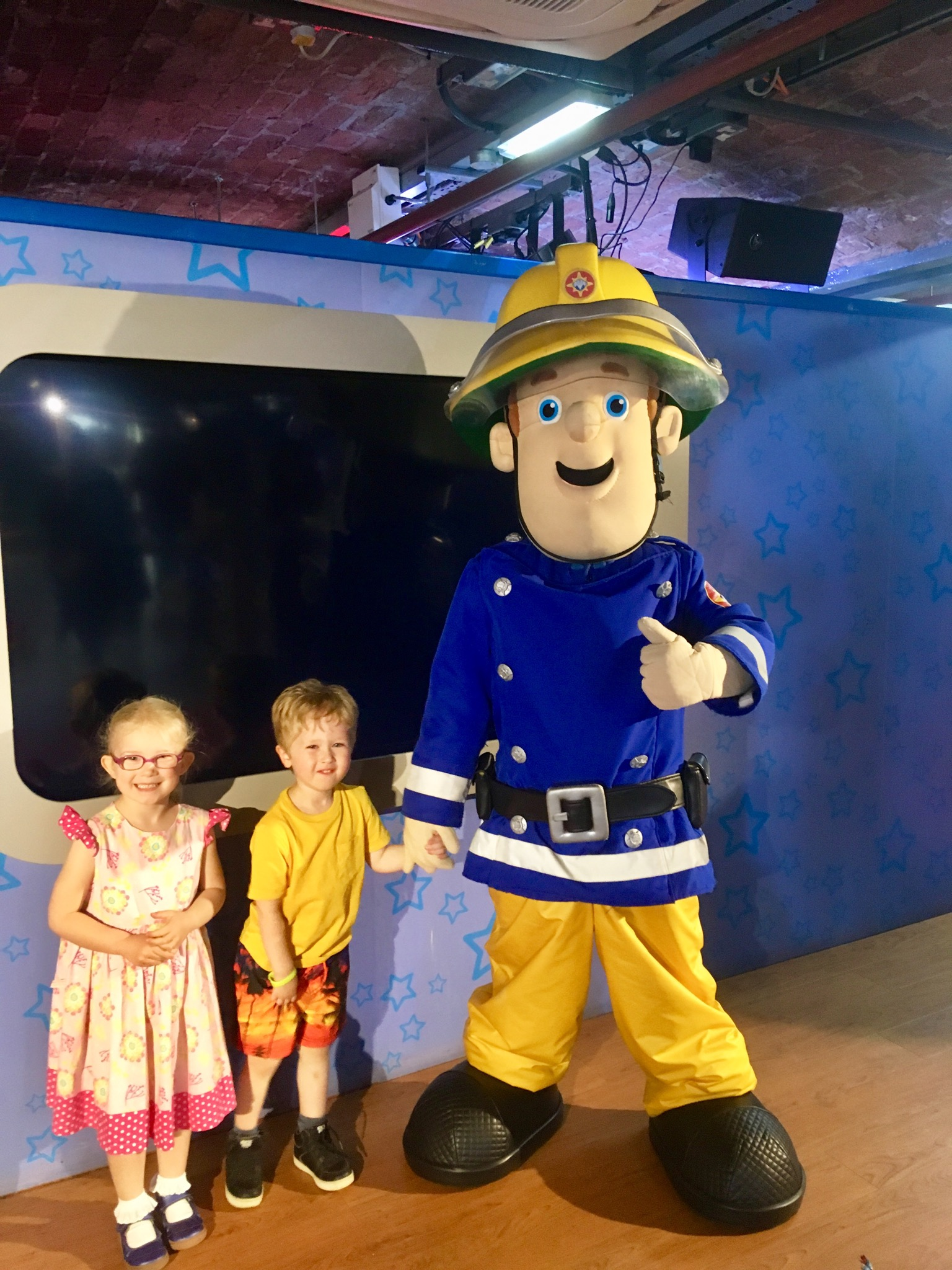 Lucas and Katie are stood next to fireman Sam