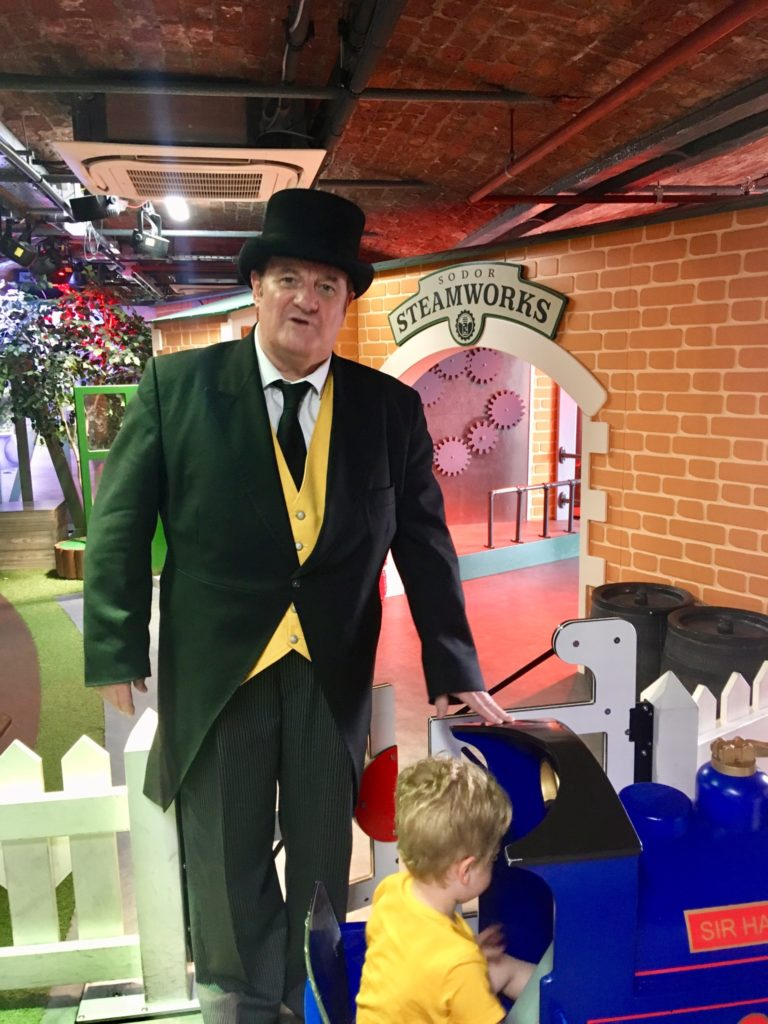 Lucas is on the small blue train and the fat controller is stood next to him