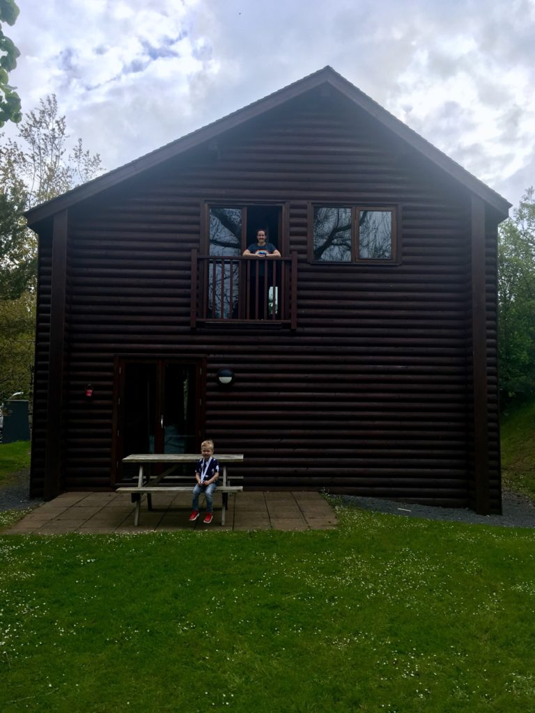 The dark brown wooden lodge. I am in the patio doors on the top level and Lucas is sat on the picnic bench outside