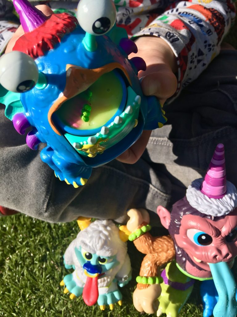 A child hands can be seen holding the barf buddy crate creature. It is blue and the slime is green. Underneath by the child's feet are the other two crate Creatures
